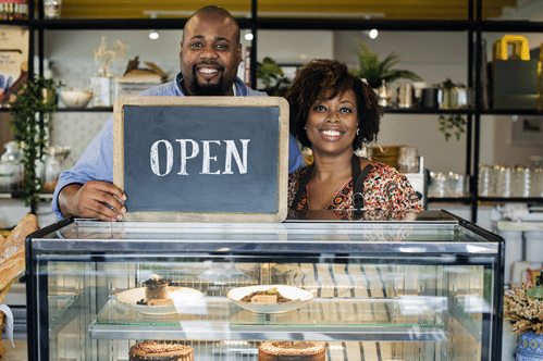 Middle-aged couple standing behind dessert counter holding an open sign.